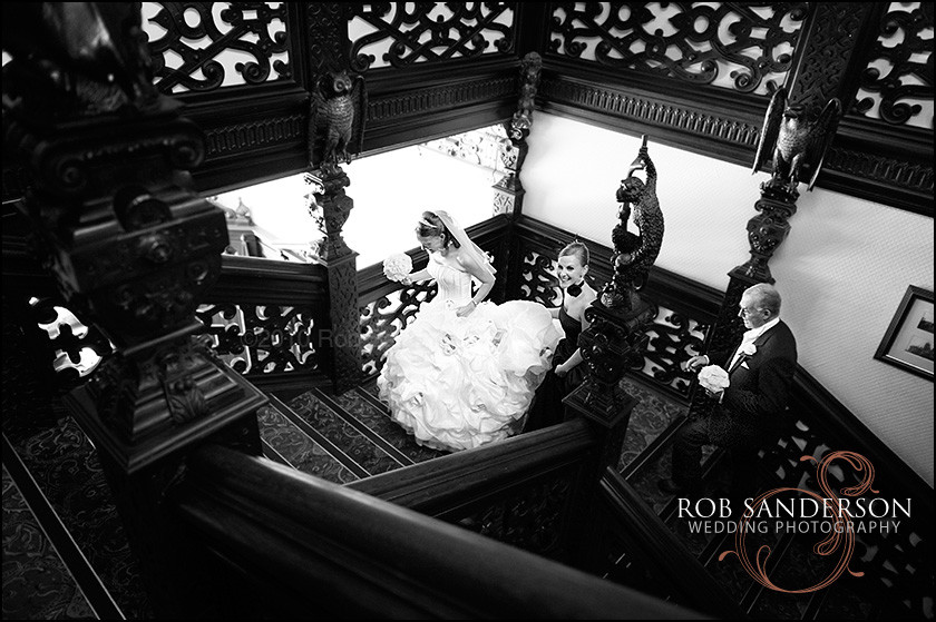 Bride makes her way up the stunning oak staircase at Crewe Hall