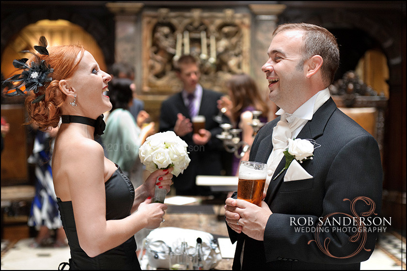 Groom shares a laugh with the bridesmaid downstairs at Crewe Hall
