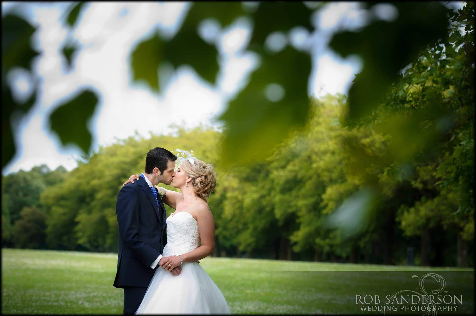 romantic picture of bride and groom kissing in Sefton Park