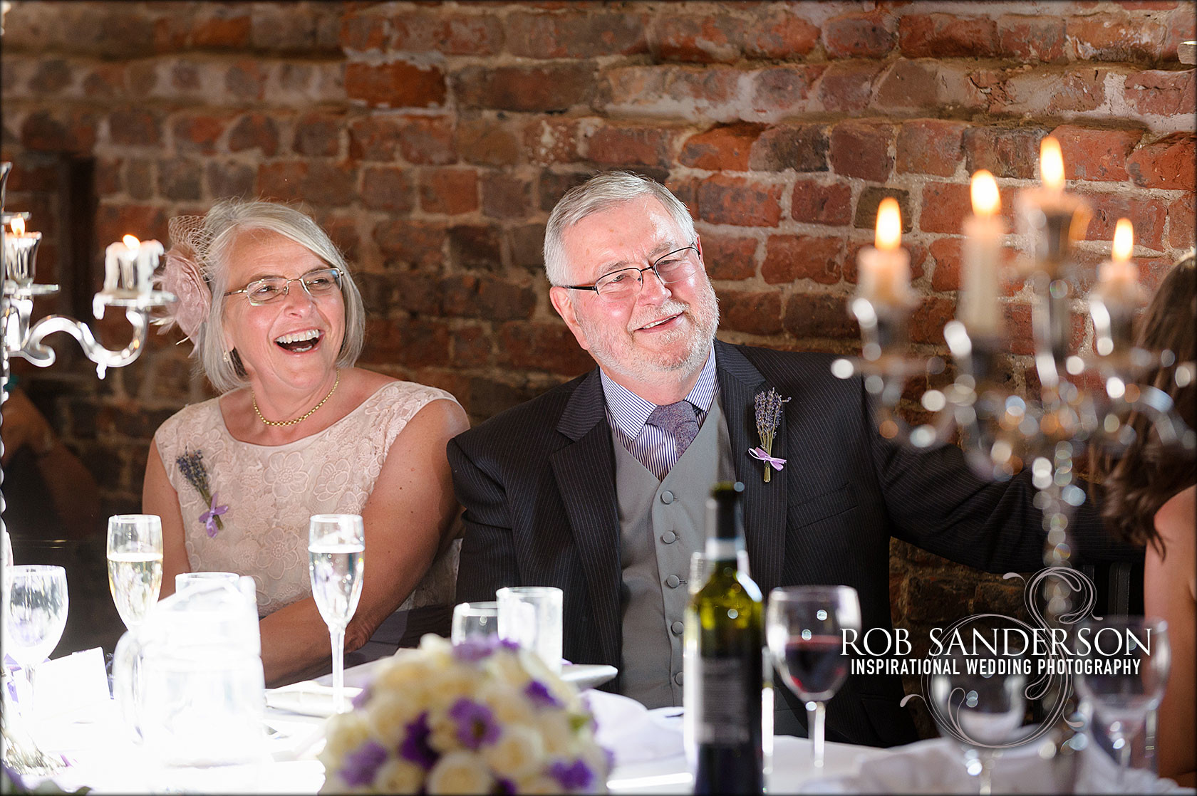 Parents of the groom laughing at the wedding speeches