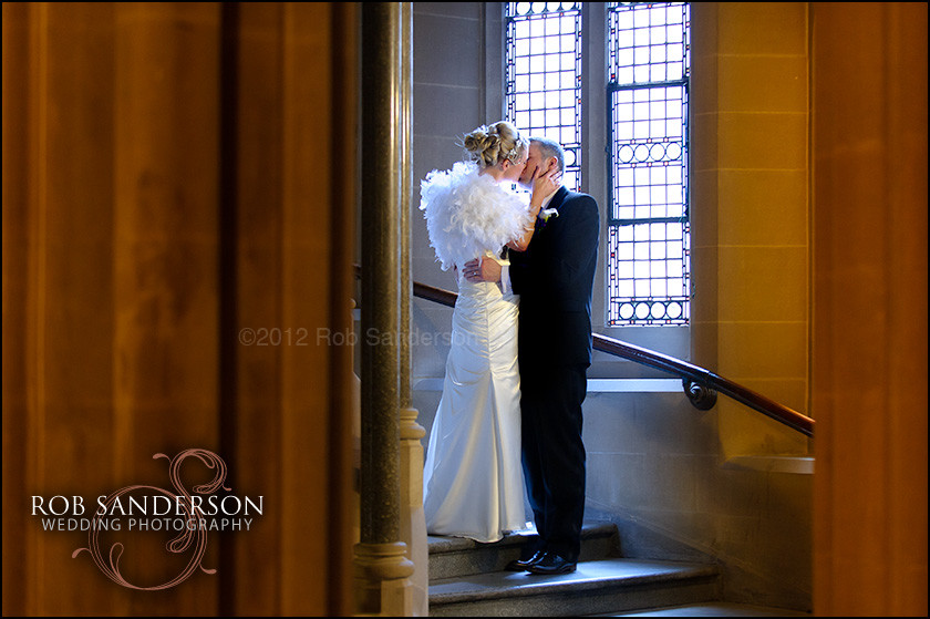 bride and groom kiss on the staircase