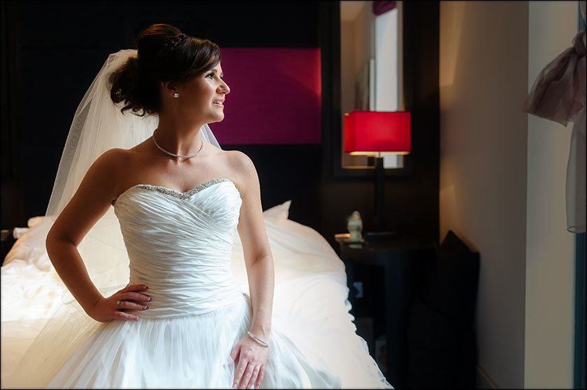 pretty bride looks out from the Malmaison before her wedding in Liverpool