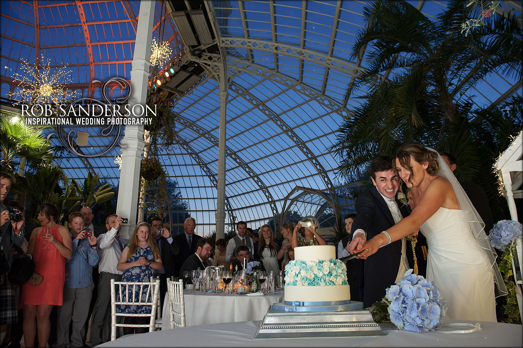 cutting the cake with spectacular view of the Palm House at night in the background