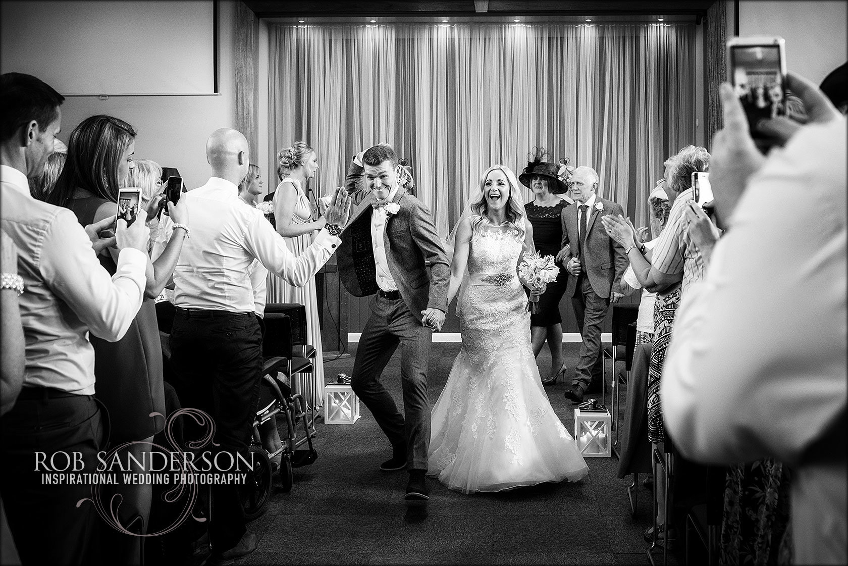 very happy groom celebrates with his bride walking down the aisle