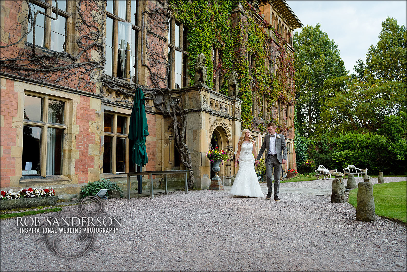young married couple stroll hand in hand outside Soughton Hall