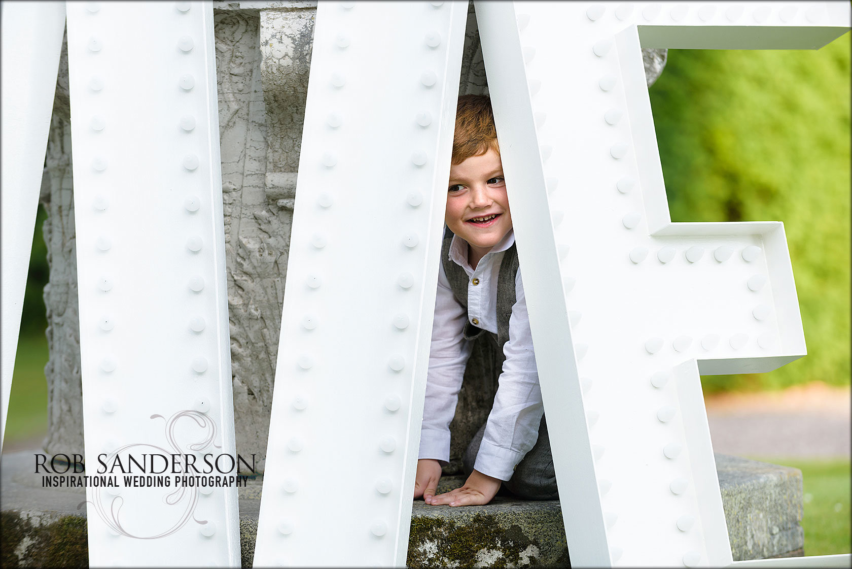 cute little boy hides behind huge iron letters that say LOVE
