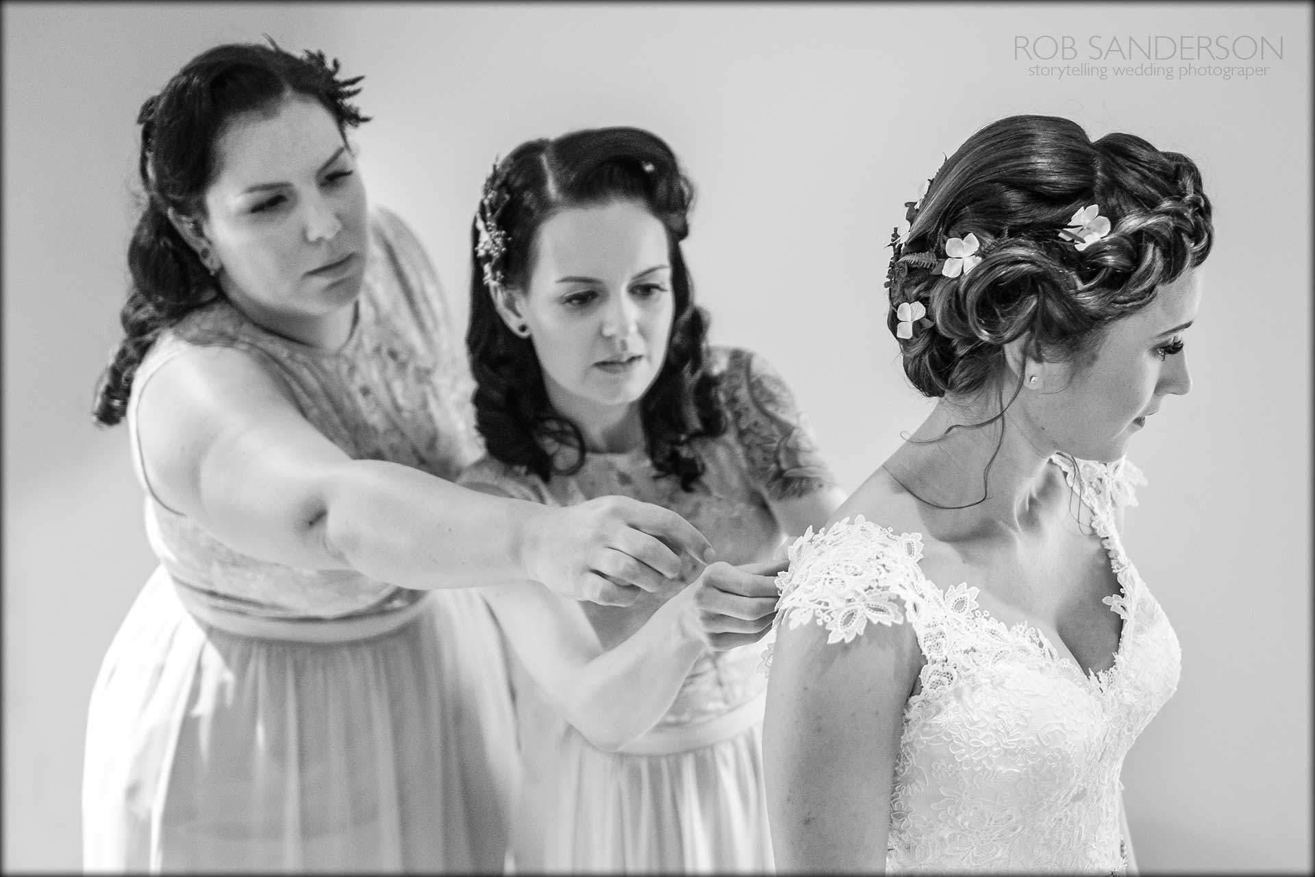 Bridesmaids help fasten the wedding dress
