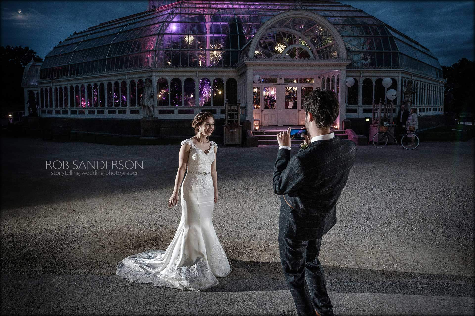 bride and groom outside outside the Palm House at nightime