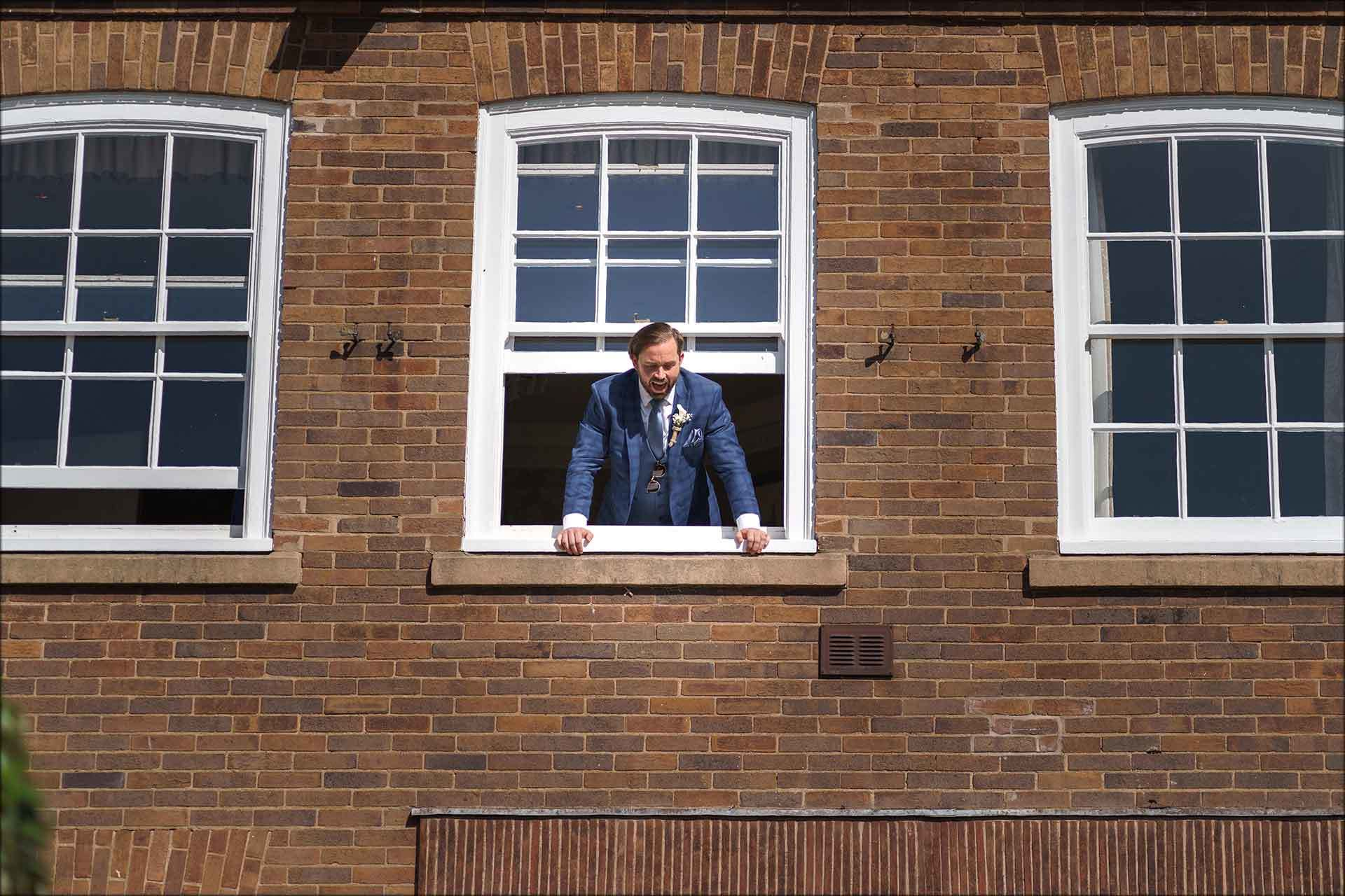 Groom looks out of the window at Delamere Manor
