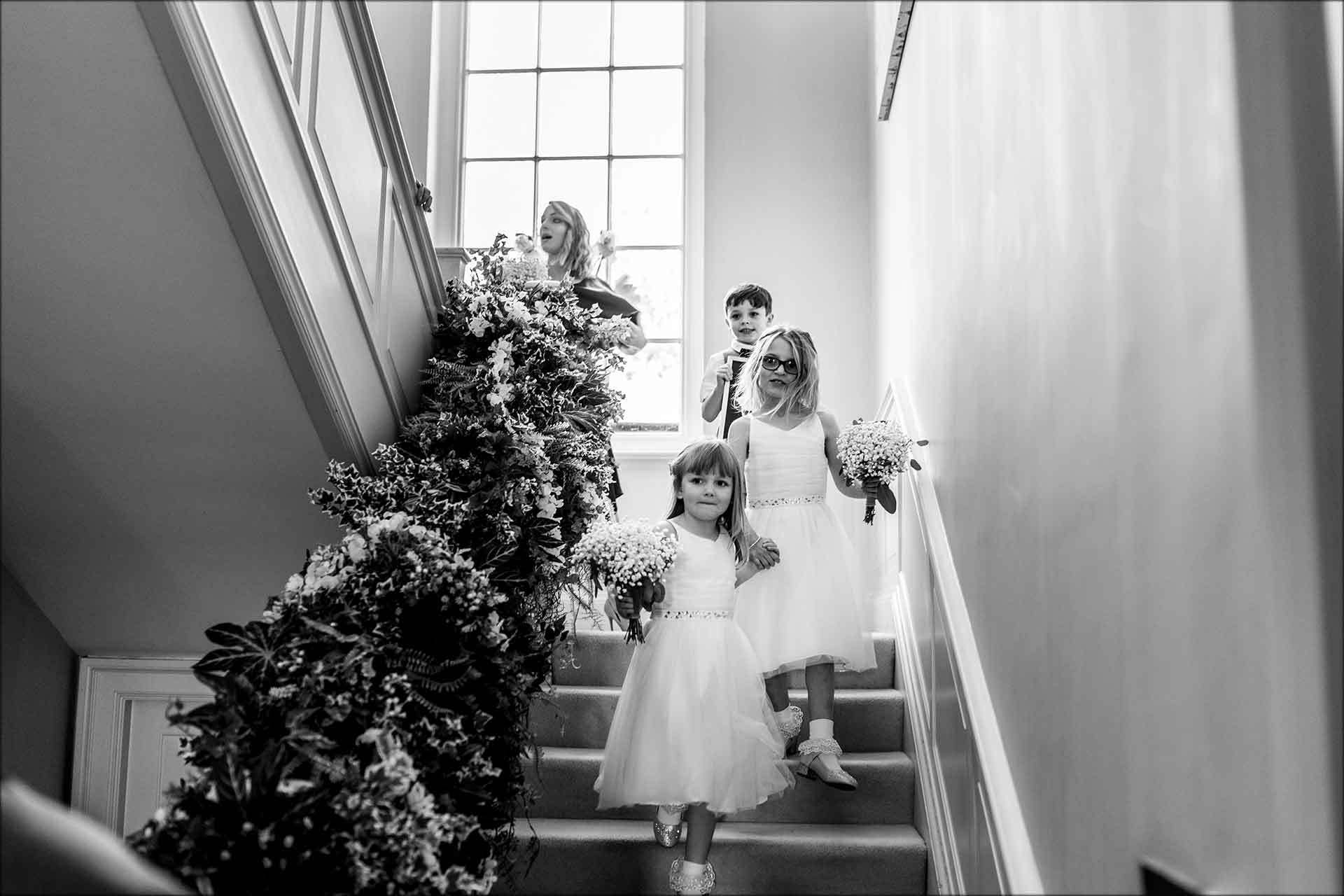 Flower girls walking down the stairs at Delamere Manor