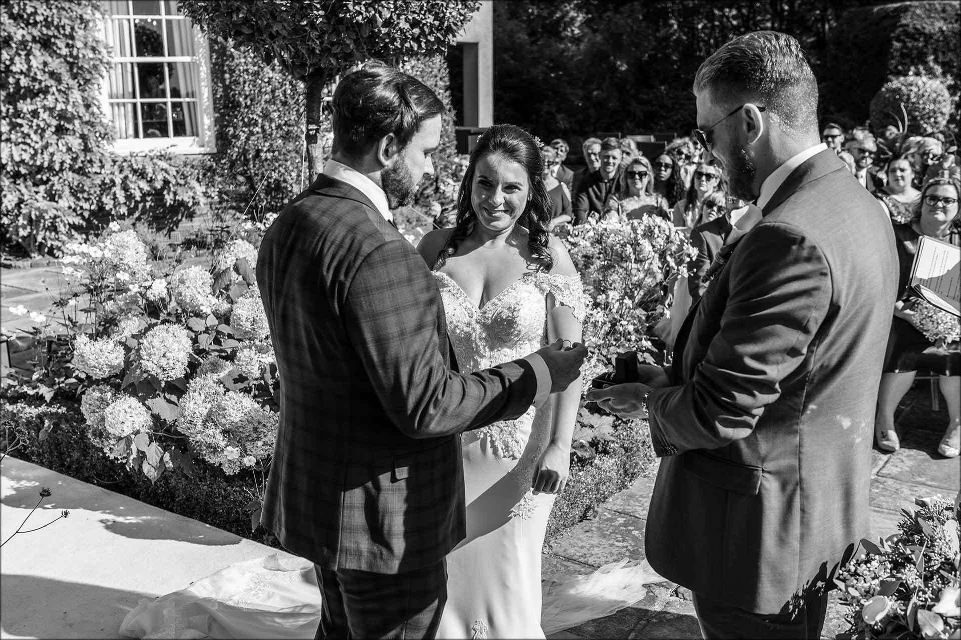 Bride and groom exchange rings during their outdoor wedding ceremony