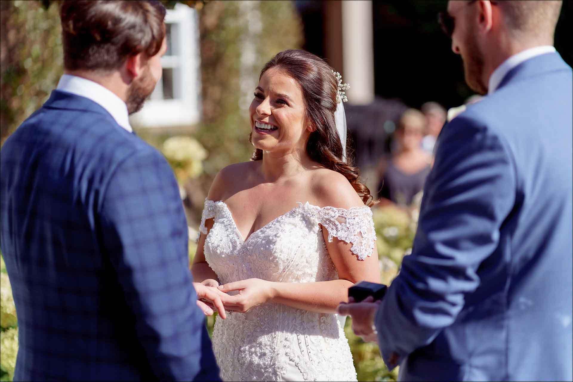 bride putting wedding ring on grooms finger