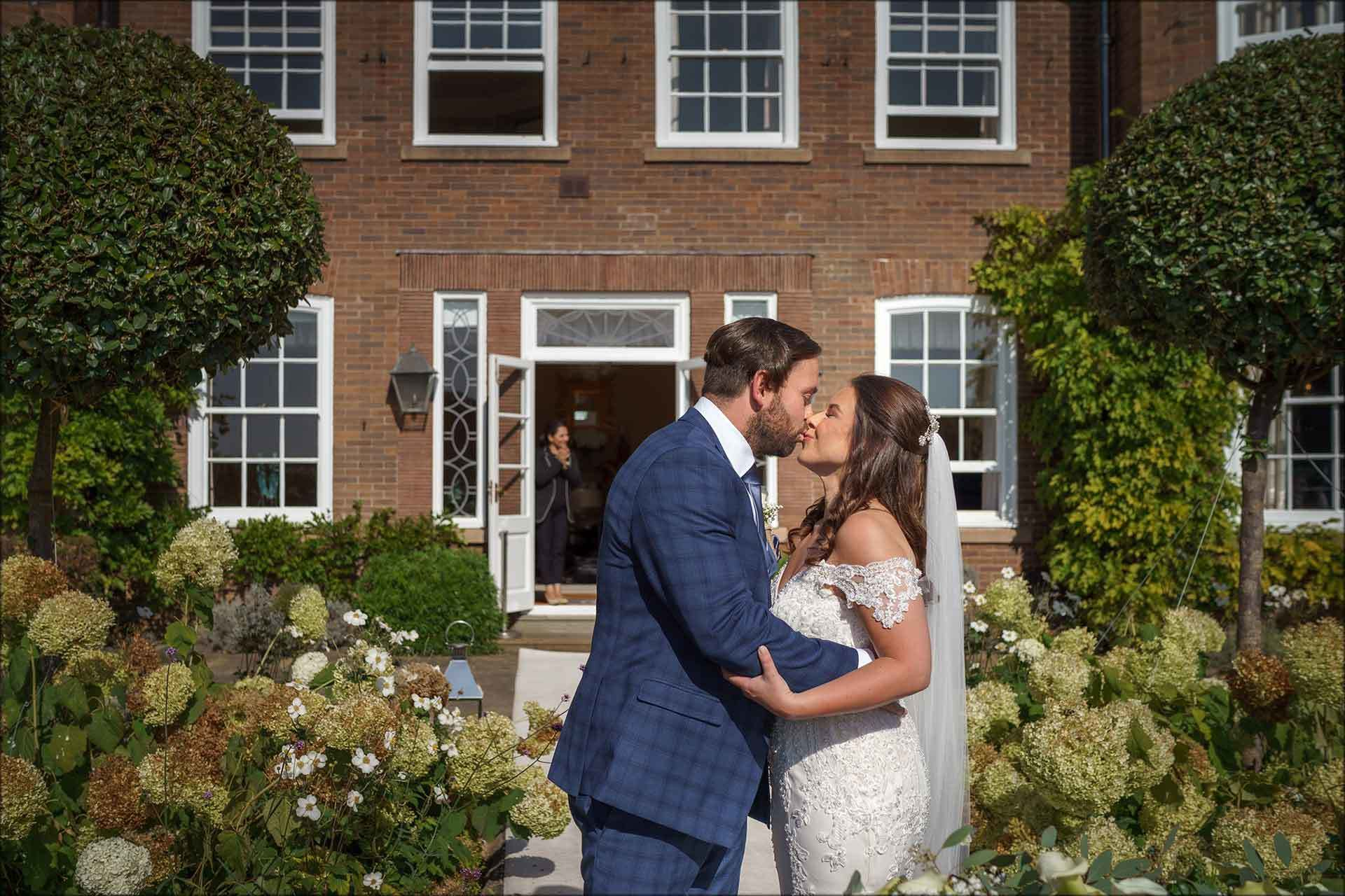 Bride and groom first kiss at Delamere Manor outdoor wedding ceremony