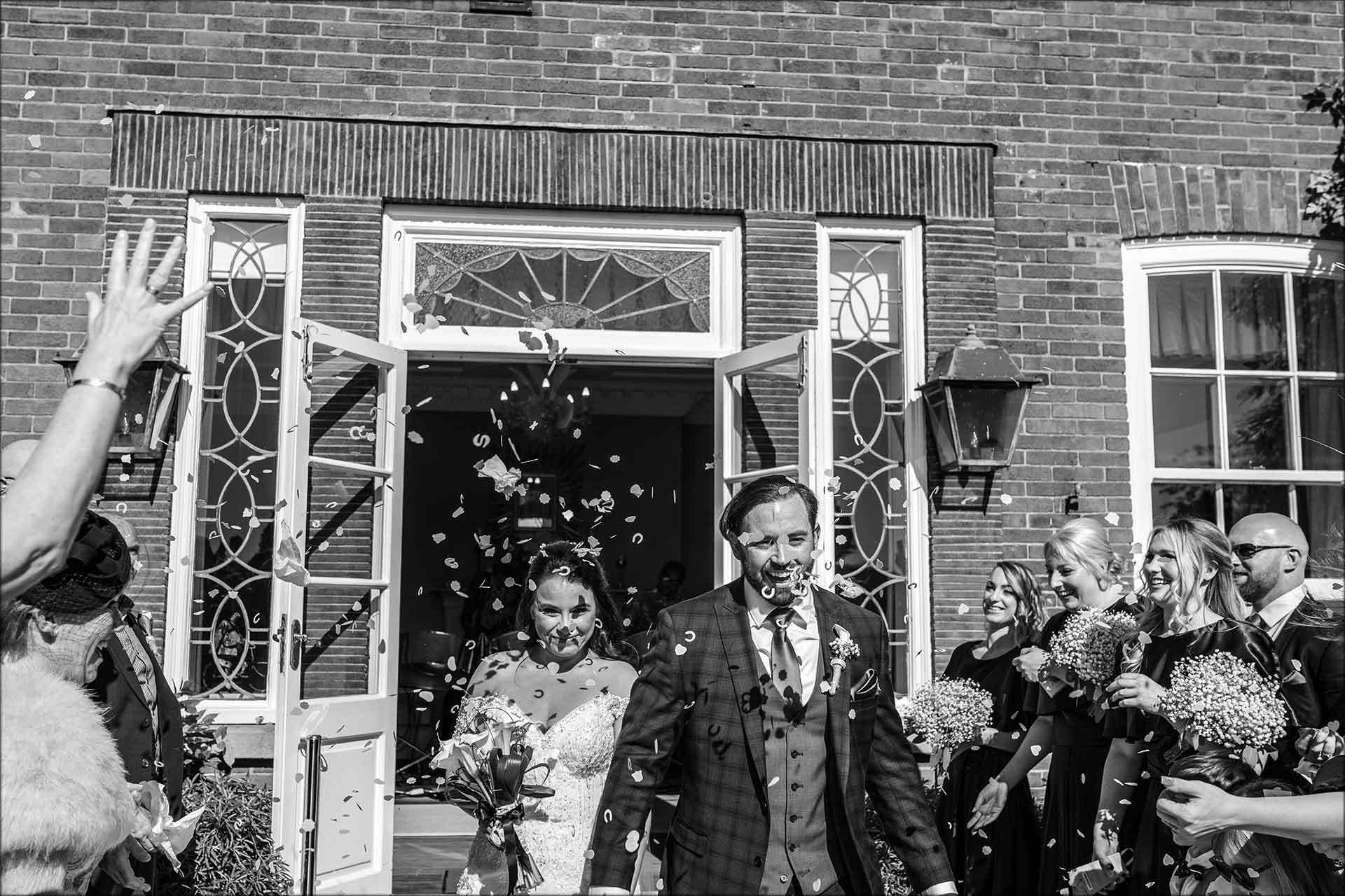 Bride and groom with confetti outside Delamere Manor