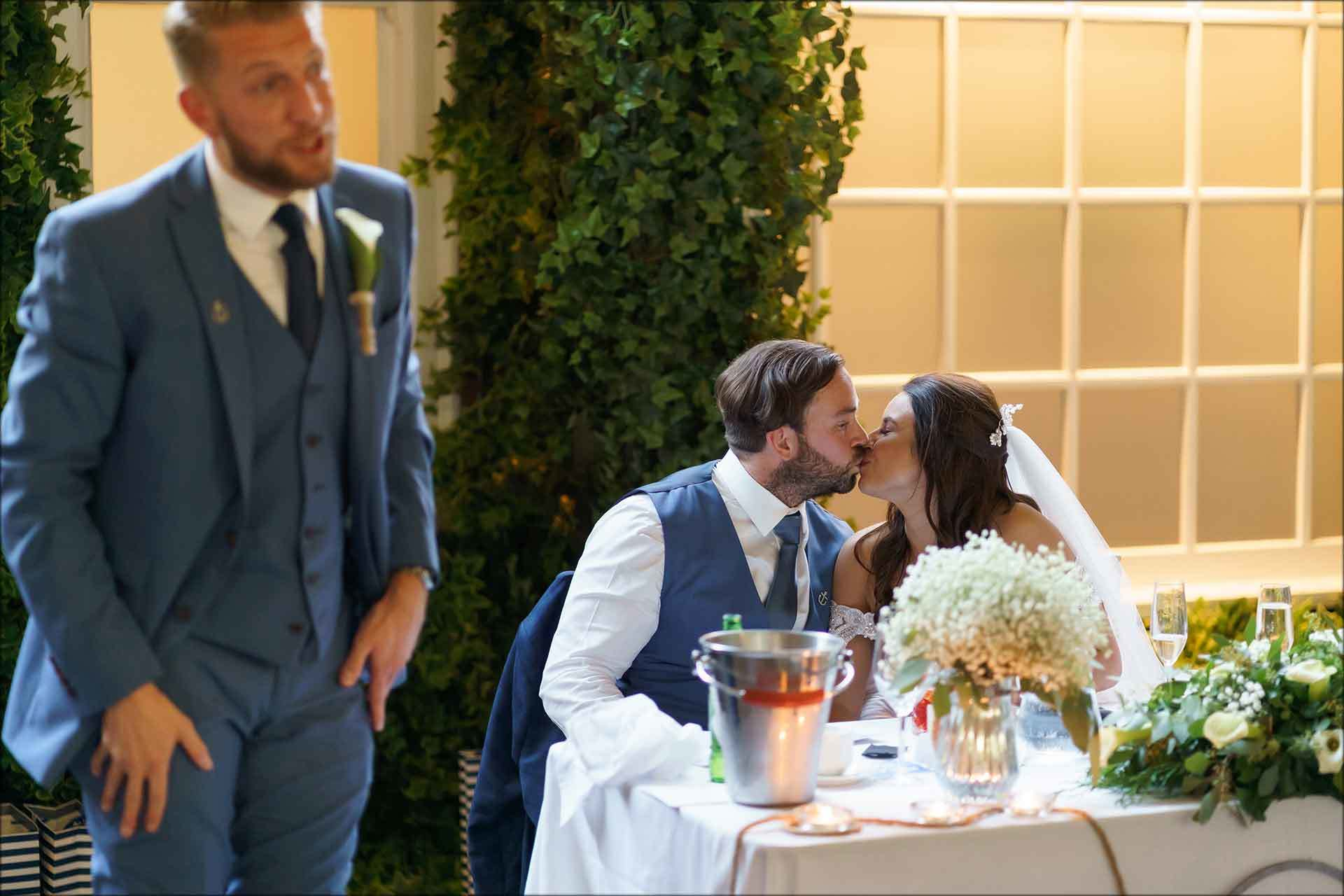 Bride and groom kissing during best mans speech