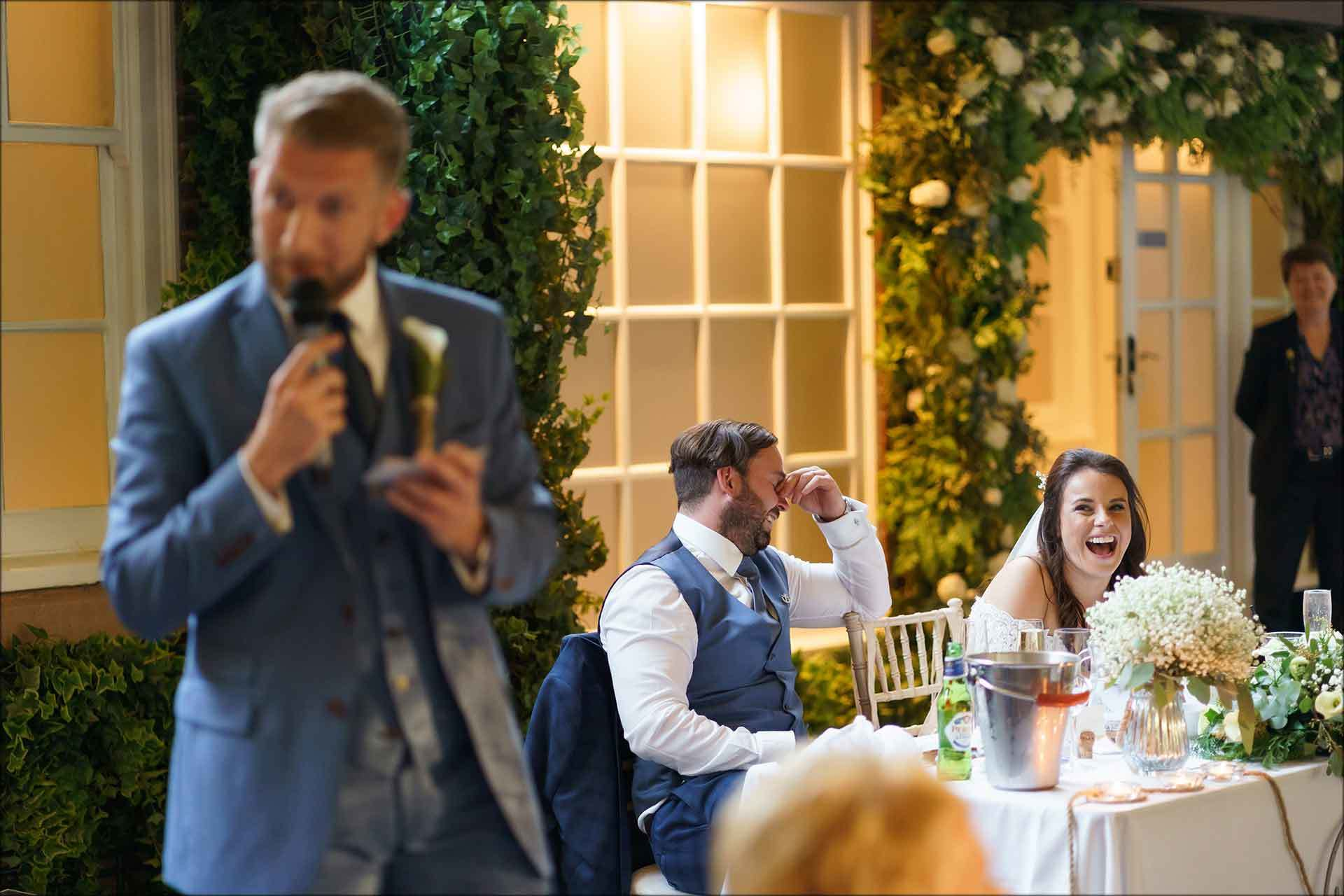 Bride and groom laughing during best mans speech