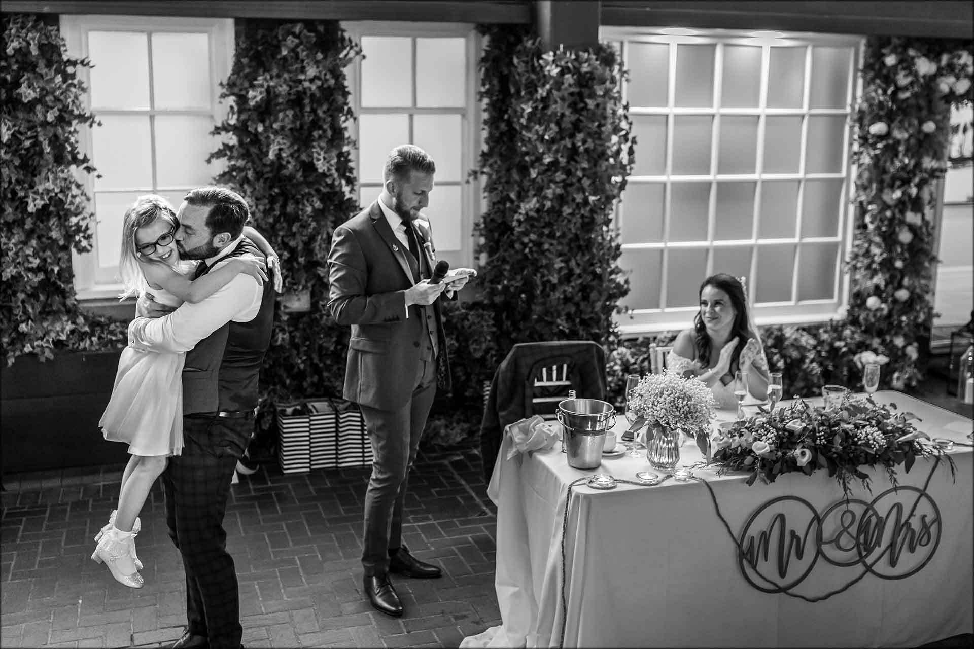 Groom kisses the flower girl