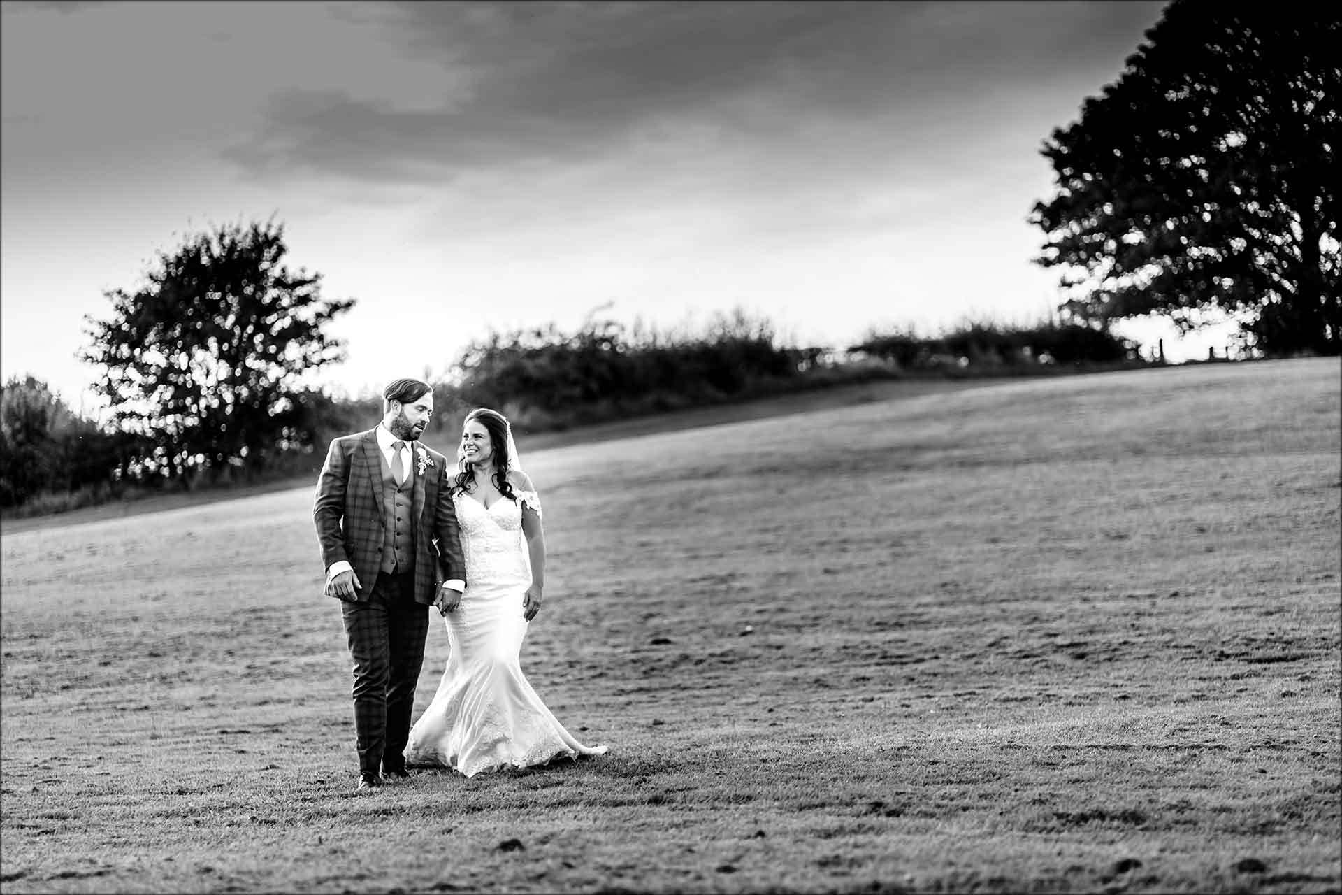 Bride and groom walking in the grounds at Delamere Manor
