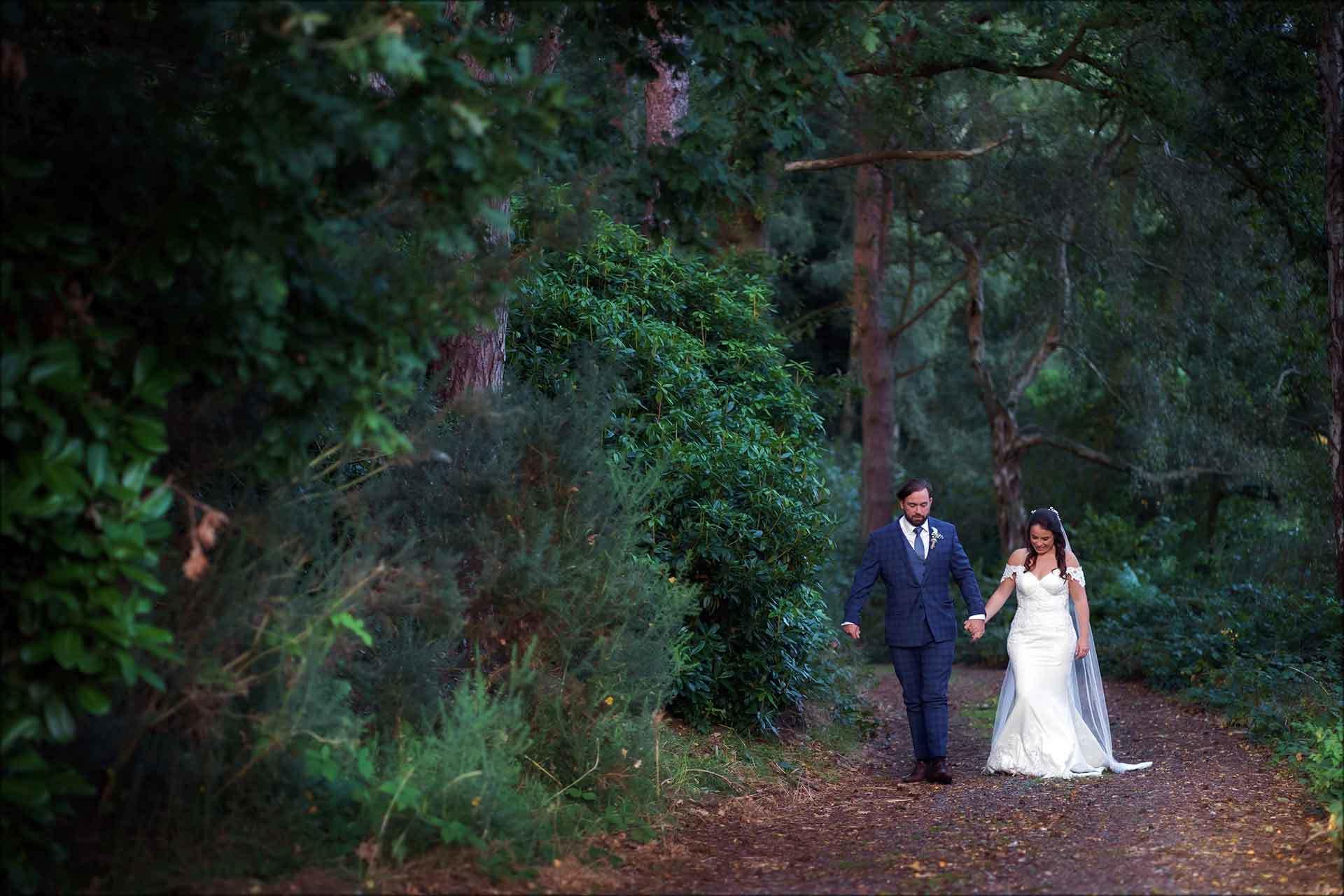 Bride and groom walking through woodlands