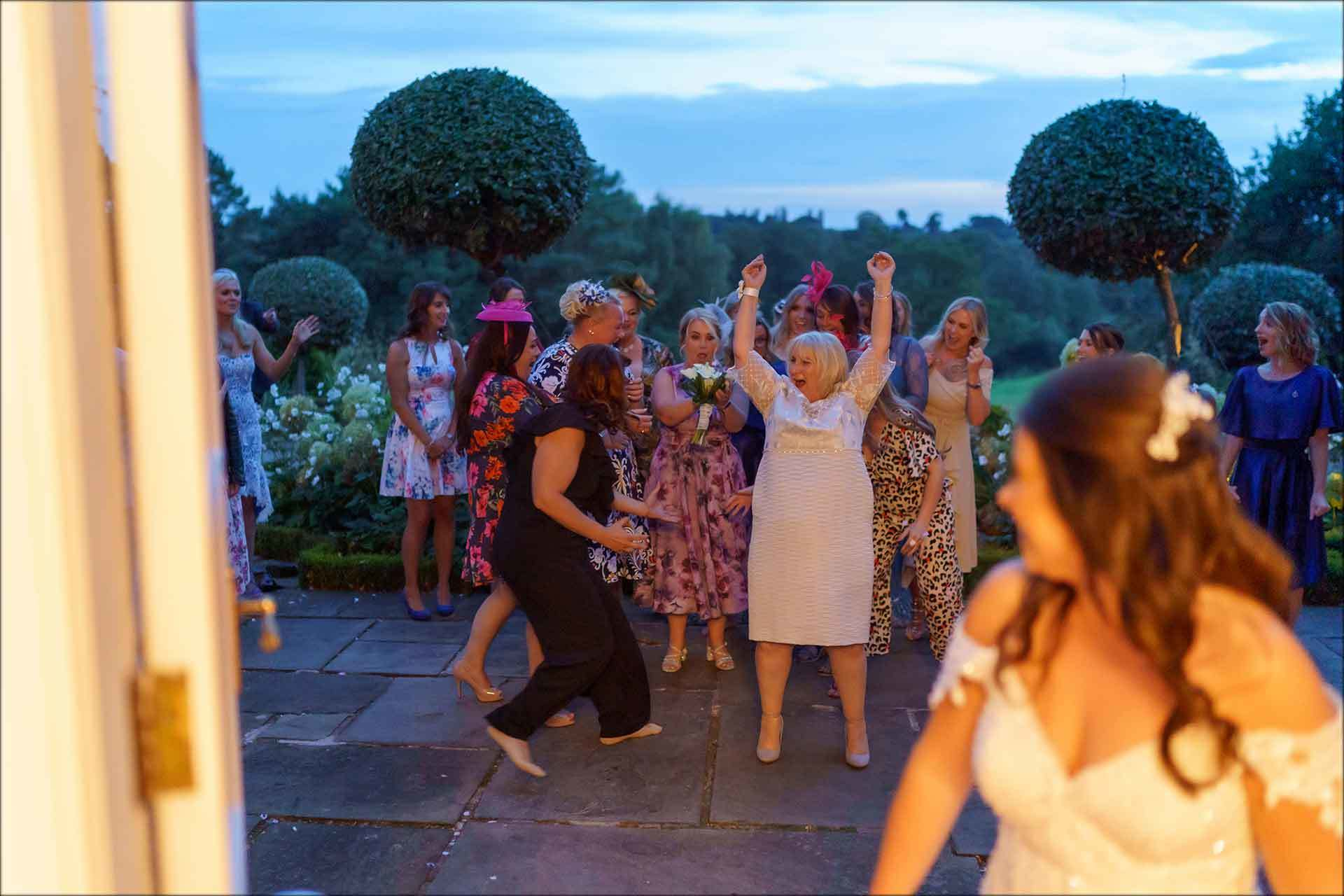 Mother of the bride tries to catch thou bouquet