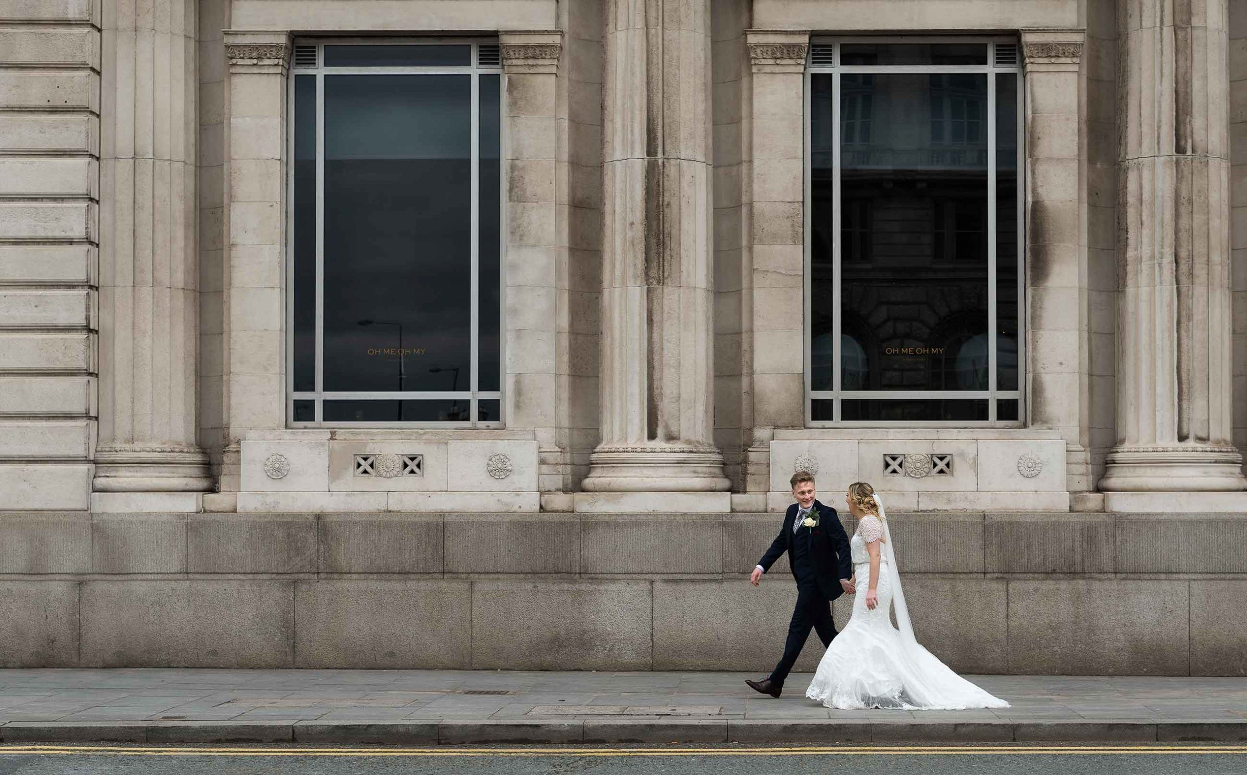 Newly married couple walking outside OH ME OH MY in Liverpool